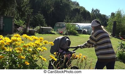 mother woman try to send baby to sleep in stroller buggy in rural garden yard near flowers. 4K