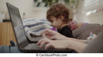 Mother working from home with toddler during COVID-19 ...