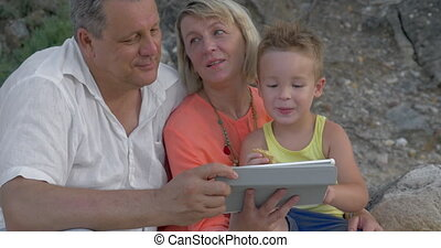 Mother,father and son watching video on pad while sitting on beach