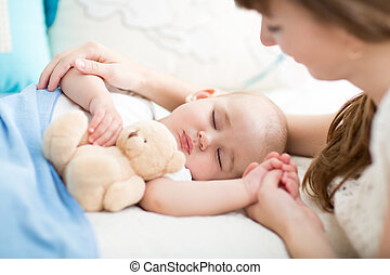 Motherhood. Parenthood. Young mother looking at her baby sleeping in bed