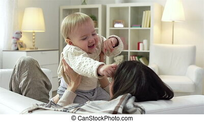 Motherhood - Slow motion of a charming young mother playing...