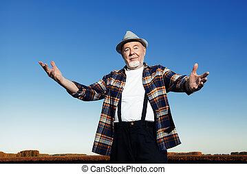 motherland - An elderly farmer standing in a plowed field. ...