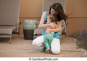 Motherly love - Young mother hugging her cute baby girl...