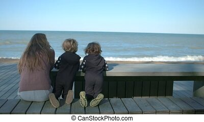 Mothers and sons are sitting at a table by the sea