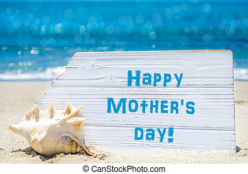 Mother's day background with seashell on the sandy beach