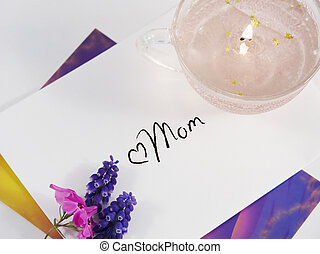 A Mother's Day card and envelope with flowers and candle.