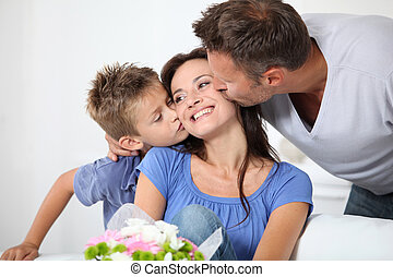 Man and son kissing woman on mother's day