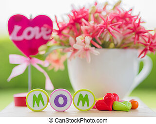 mother's day concept. LOVE MOM alphabet with colorful heart and flower on background