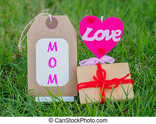 mother's day concept. LOVE MOM text with colorful heart and gift on green grass background
