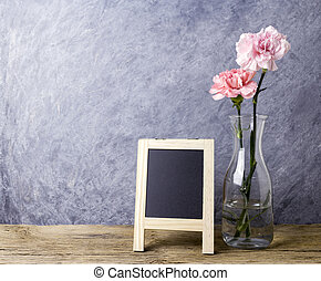 Mothers day concept of pink carnation flower in clear bottle and blank chalkboard on old wood with copy space