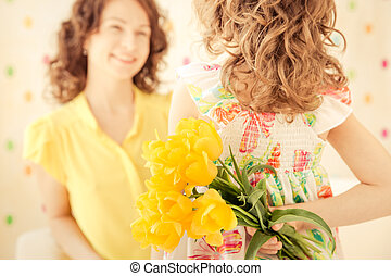 Woman and child with bouquet of flowers at home. Spring family holiday concept. Mother's day