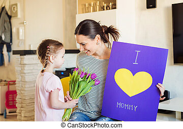 Mothers day, girl giving flowers and card to her mum -...