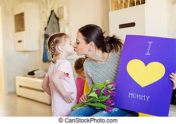 Mothers day, girl giving flowers and card to mom