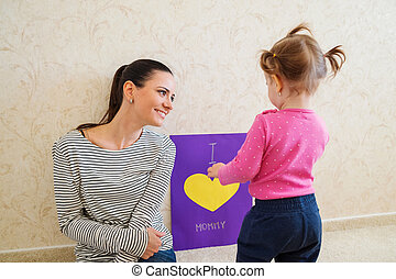 Mothers day, girl giving greetingcard to her mum