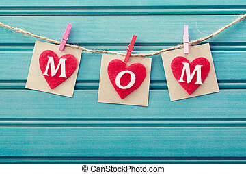 Mothers day message on felt hearts over blue wooden board