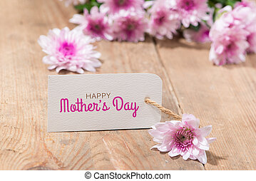 Mothers Day. Tag paper with color flowers on wooden background. Top view. Mock up