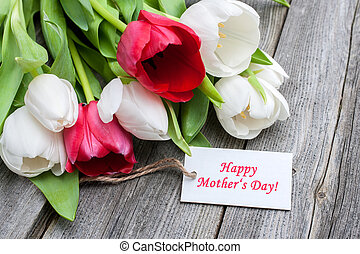Tulips with tag and text for mother's day on wooden background