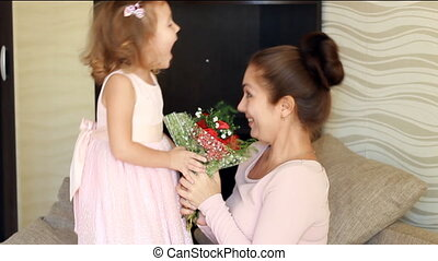 Mother's day. Woman and her child girl with a bouquet of...