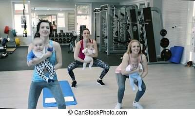 Mothers exercising with babies in gym, doing squats.