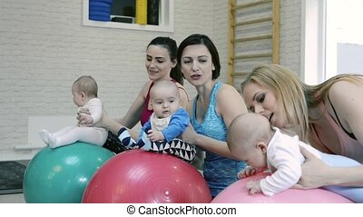 Mothers exercising with babies in gym on gymnastic balls.