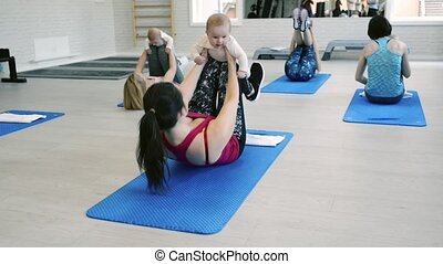 Mothers exercising with babies in gym with personal trainer.