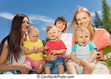 Mothers holding cute babies sitting together