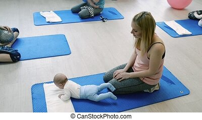 Mothers with babies in gym on exercise mats with personal trainer.