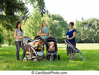 Portrait of happy mothers with baby carriages standing in park