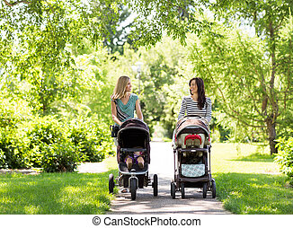 Mothers With Baby Carriages Walking In Park - Happy mothers...