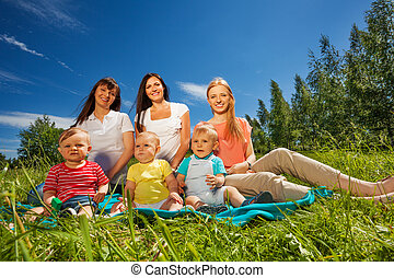 Mothers with their toddlers sitting in the meadow