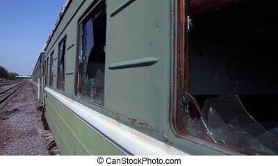 Motion along abandoned train, broken windows at railcar