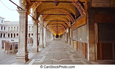 Motion along arch passage decorated with fairy lights with closed shops on ancient St Mark square during coronavirus lockdown