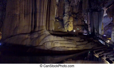 motion along bizarre stone terraces in Paradise Cave -...