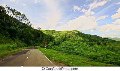 Motion along Country Curvy Road among Hilly Landscape under...