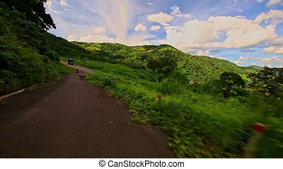 Motion along Curvy Country Road among Green Hilly Landscape...
