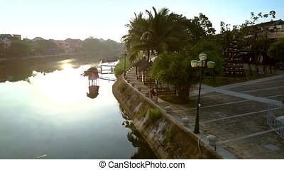 motion along nice modern riverfront with palm trees to woman doing fitness in ancient Hoian in morning