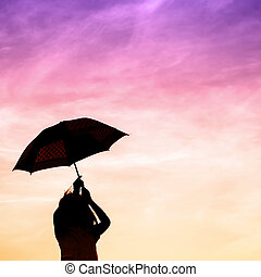 Motion blur jumping Umbrella girl with sunset silhouette, copy space