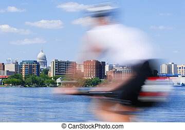 Motion blur of a person riding a bicycle past the skyline of madison wisconsin and Lake Monona
