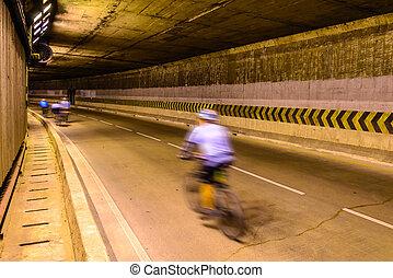 Motion blur of cyclist in underground road.