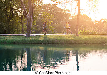 Motion blured of runner are running in urban park with water reflection.
