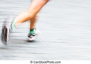 Motion blurred runner's feet in a city environment - running marathon (panning technique used -> motion blurred image; color toned image)