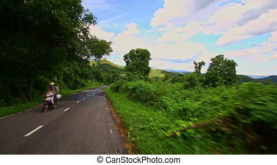 Motion down Country Curvy Road among Hilly Landscape under Sky
