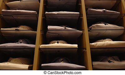 Motion down past shelving with collection of stylish folded pastel men shirts in brightly lit fashion store low angle shot