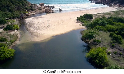 motion from dark river water to sandy beach and ocean