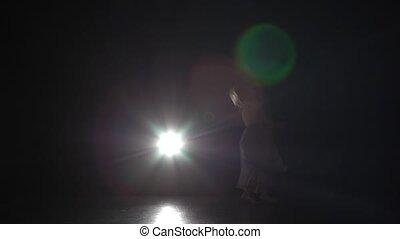 Motion of a beautiful woman dancing contemporary in dark studio.