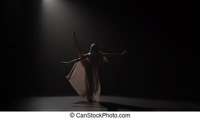 Motion of a girl practicing contemp in dark studio. - Motion...