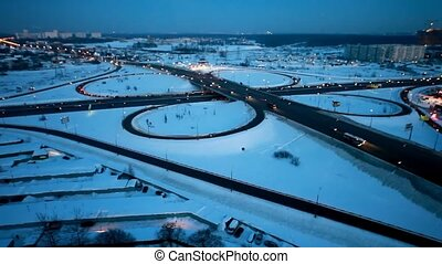 motion of cars around a crossroads on winter highway -...