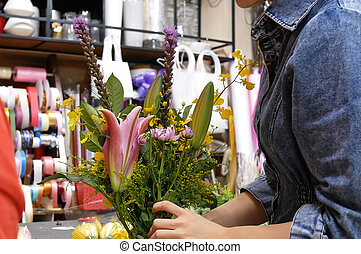 Motion of florist prepares a bouquet of flowers for customer