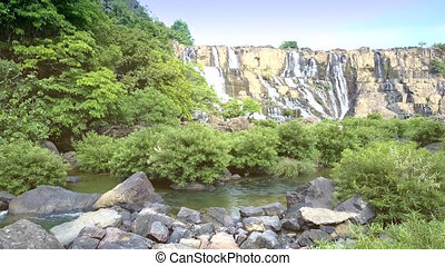 motion over round stones to brushwood at waterfall - aerial...