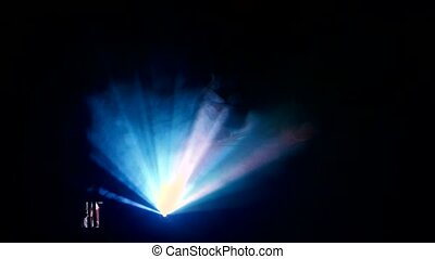 Motion picture projector in action, dark smoky room. Black background